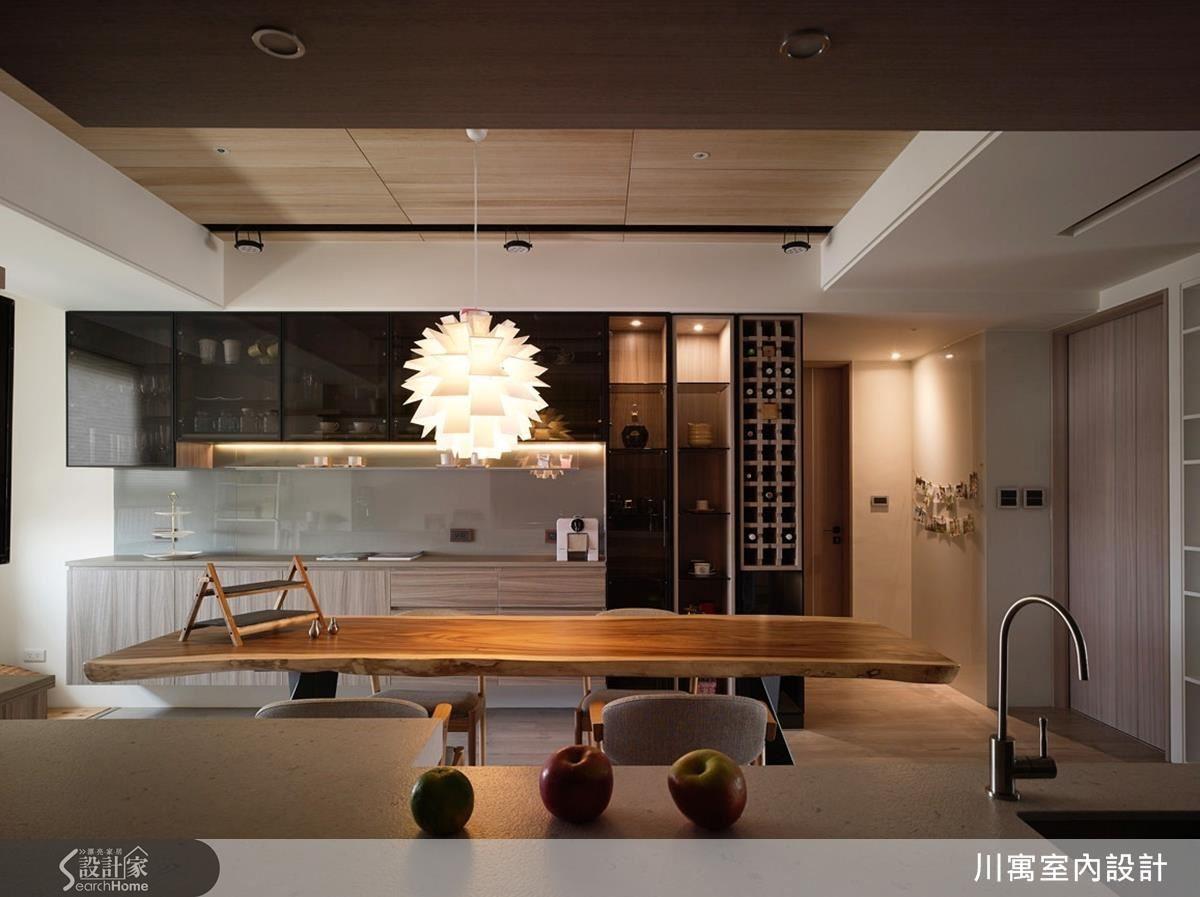 餐桌的另外一面擺放咖啡機、杯盤和酒櫃空間,黑玻櫃體收納看起來簡潔,開啟燈又能轉變成現代時尚的展示櫃。