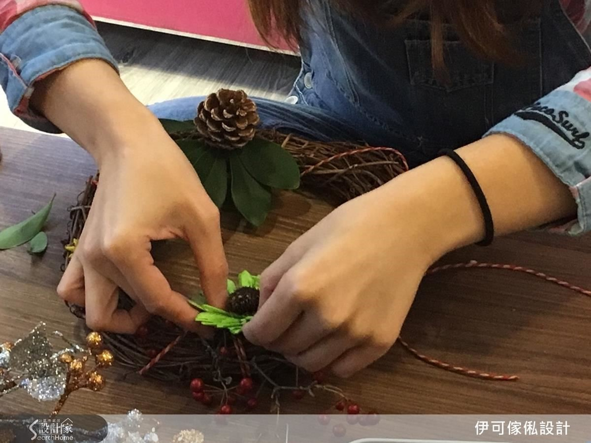 不用急著黏著固定,先在藤圈上決定大致的擺放位置,特別凸顯紅色、綠色的元素,營造出視覺焦點。