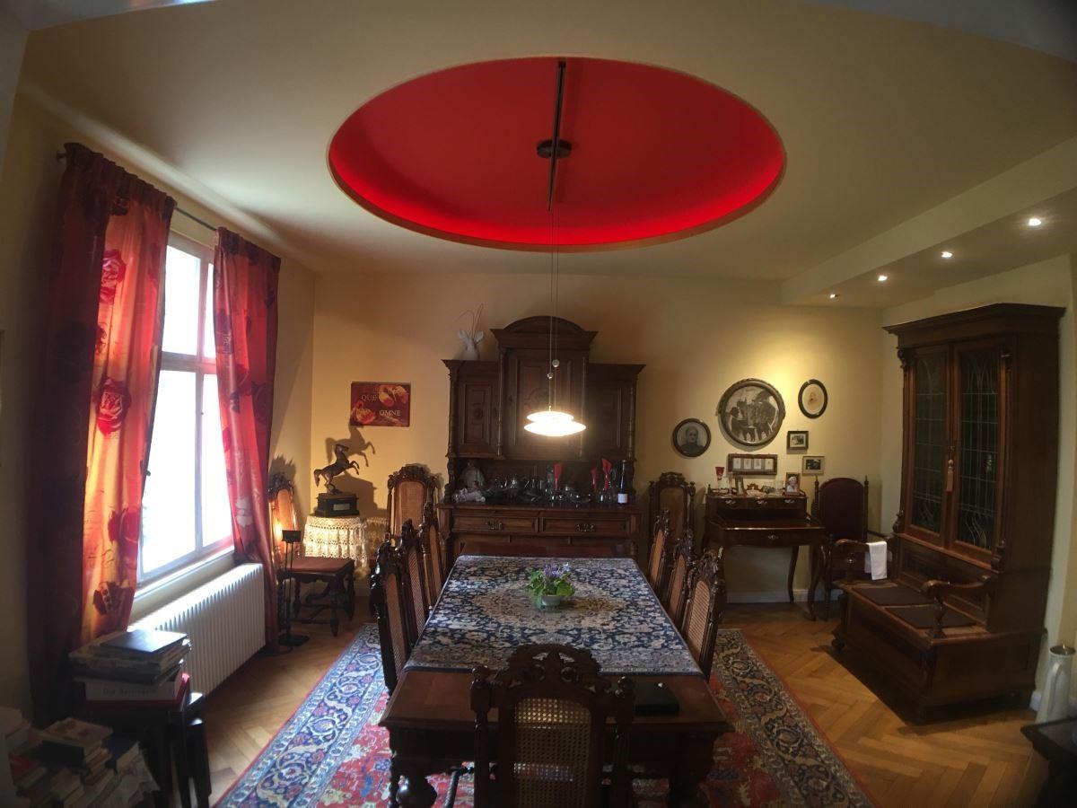 好客屋主夫婦平時喜歡邀約朋友到家裡聚會。設計時保留了 1908 年所留下來的白色門片,讓客廳及餐廳做連接,紅色古董地毯呼應了天花紅色圓型設計,在百年餐桌、櫃子的薰陶營造下,如置身於舊世紀般享受精緻的美食。