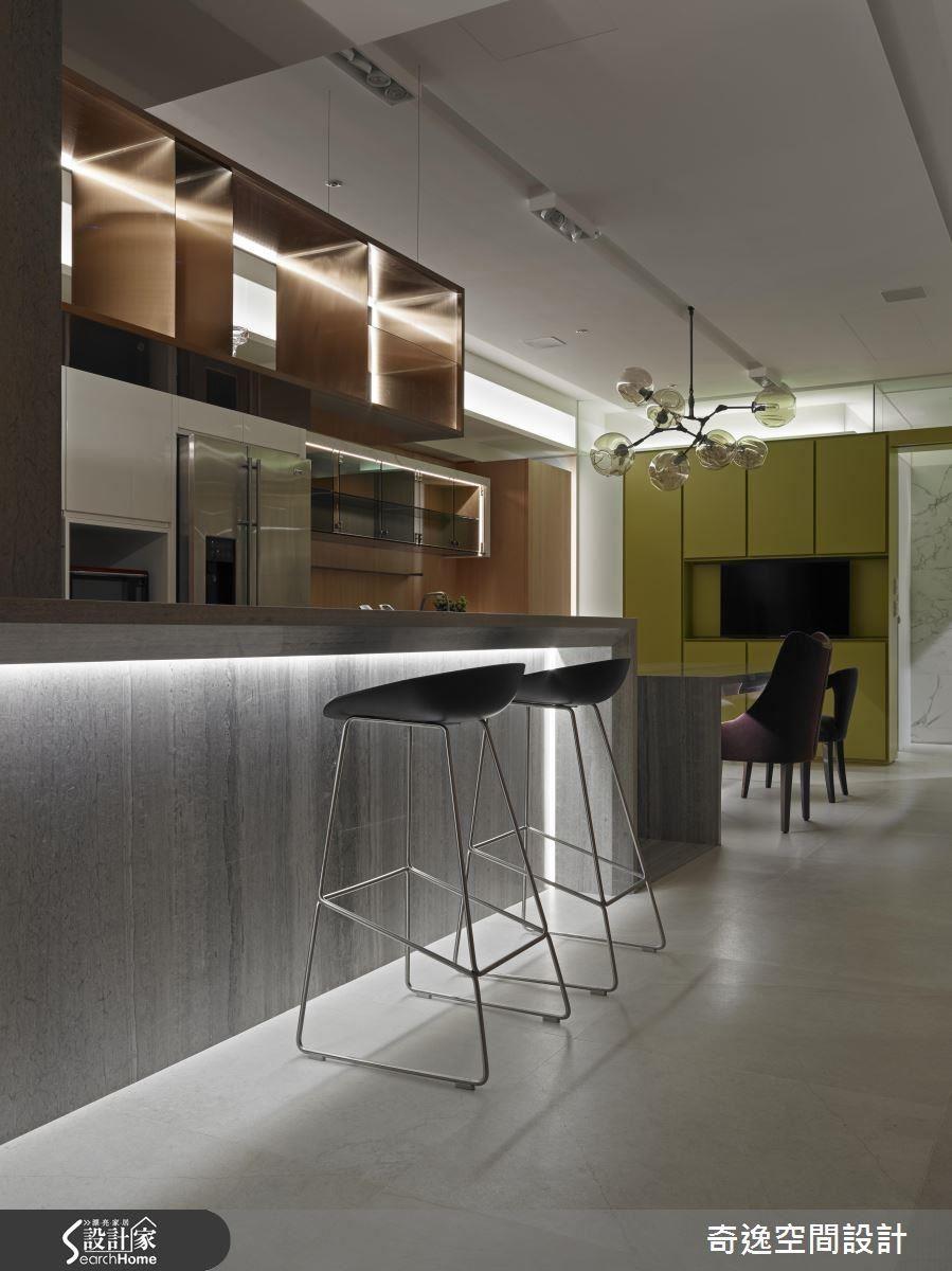 水木紋石材從餐桌延伸到吧檯,串聯出餐廚區的軸線,在簡單素雅的色調中,不同需求的櫃體也形成有趣的方塊層次,並細膩地以燈帶變換生活情境。