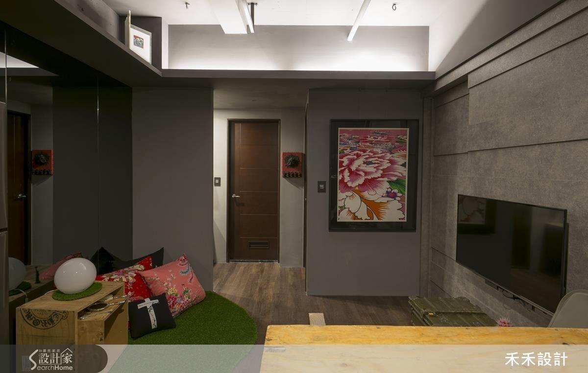 從廚房望向主臥與衛浴間的方向。圖右的電視牆為原有裝潢,僅在表面貼上新的牆面飾板。原有的天花拆掉,只保留周遭的間接照明與天花,並在四個角落及小樑旁邊加裝吊環與吊桿。圖左的大片灰鏡可協助屋主確認健身動作的正確性。
