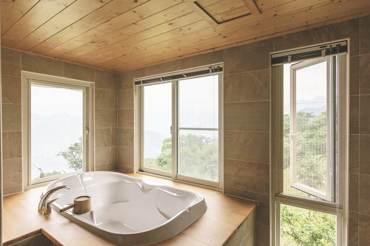 雙面採光的浴室視野一級棒,浴缸旁以北美黃檜包覆,泡澡後起身坐著也不嫌冷,而且高度恰巧符合人體工學。攝影_葉勇宏