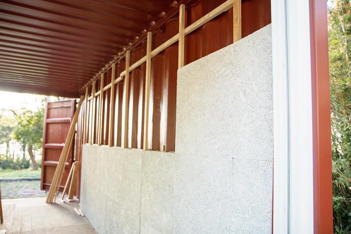 於貨櫃內層安裝隔熱鑽泥板,這是為建築物作出阻熱的重要步驟。