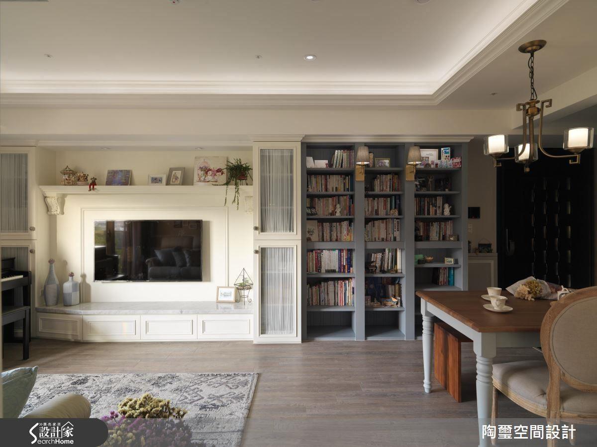 電視牆以恬靜的奶油白與灰藍色書櫃,不但在公領域營造出鮮明色彩的對比,也區分了兩個空間的隱性界定,巧妙修飾偏長的格局比例。
