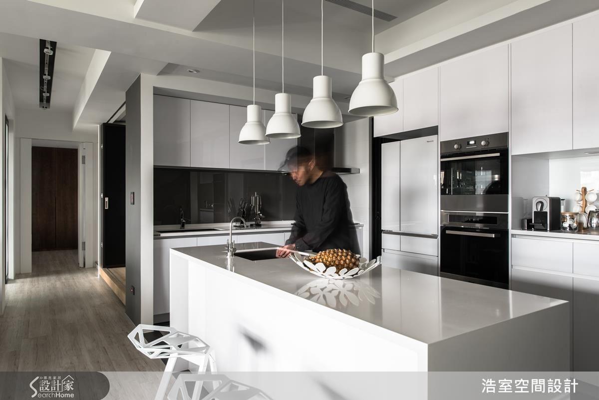 愛下廚的主人要求廚房空間一定要夠大,開放式的廚房範圍至少 4~5 坪,比 1 個小房間還寬廣。賽麗石的白色中島是料理舞台,而流理台則藏身寬度 60 公分以上、塗有黑板塗料的外框中,垂吊而下的燈具與造型特殊的椅子成為目光焦點。