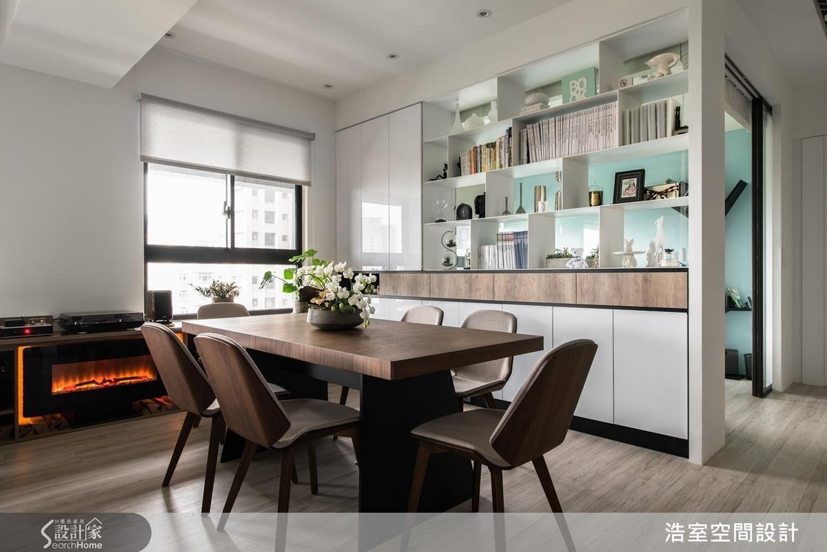 另外,沙發後方餐桌空間做出透明玻璃展示隔間牆,書房裡的藍綠牆面因此透出牆面,成為客廳中另類亮點,電子壁爐的火光、木色腰帶,在在都為白色空間注入人文的溫暖。