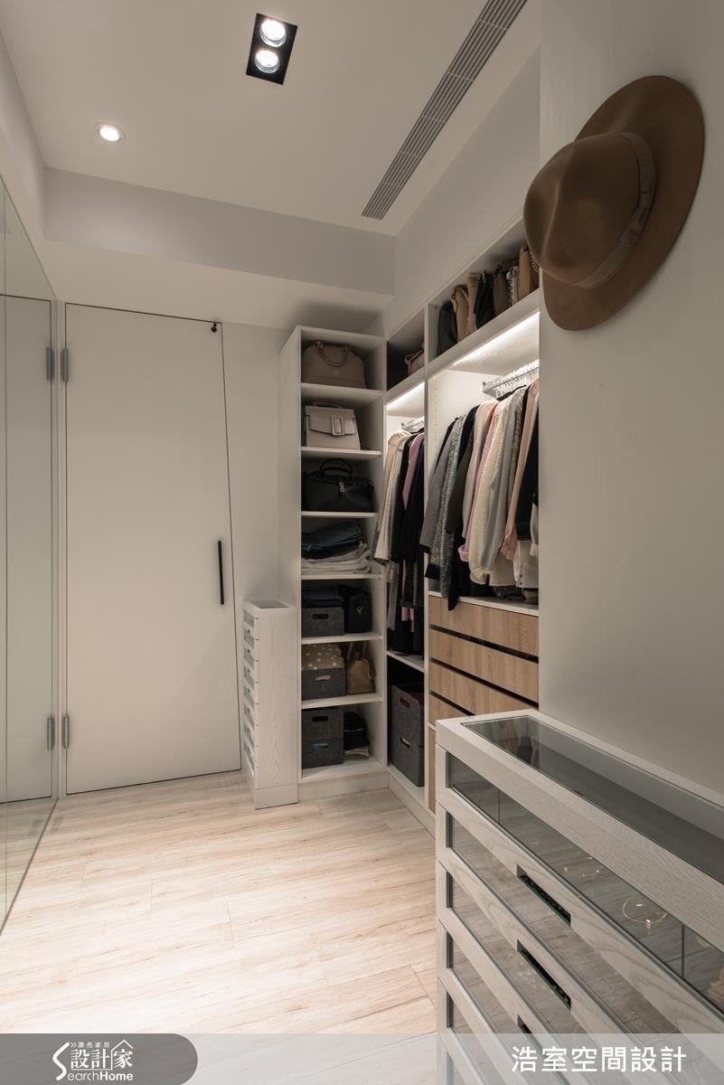 至於主臥範圍裡的更衣室,以斜面設計出入口,也隱藏在白色牆面中。空間內收納機能十足,無論包包或衣帽,連主人收藏眾多的眼鏡都一一歸位,整面牆的穿衣鏡則是擴大了視覺空間。