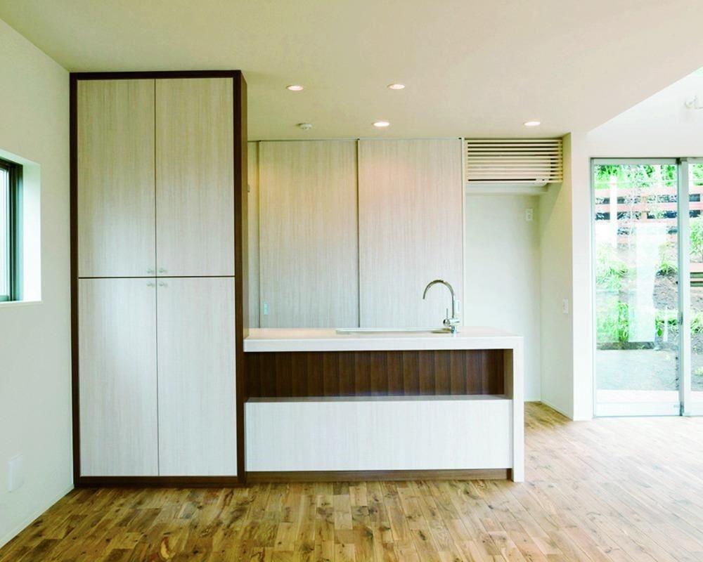 從餐廳往廚房望去。瓦斯爐和抽風扇都隱藏在左邊的收納櫃。(「丘上之家」設計:Far East Design Lab 攝影:大倉英揮)