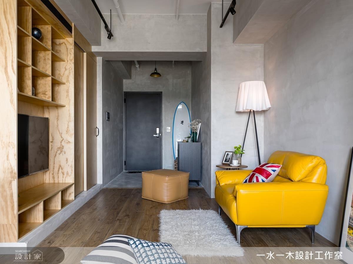 玄關到客廳處,為了強化原先 L 型格局缺點,以一致性材料鋪設牆面,延展空間線條,製造放大視覺感。
