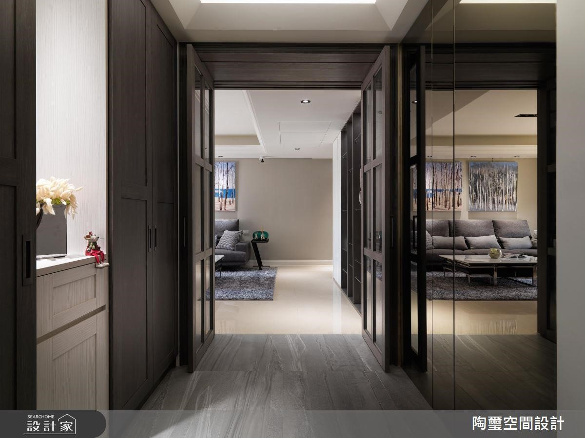 玄關右側加上銅色的穿衣鏡設計,不但隱藏了儲藏室的位置,藉由鏡面的映射效果,更讓玄關放大了兩倍。