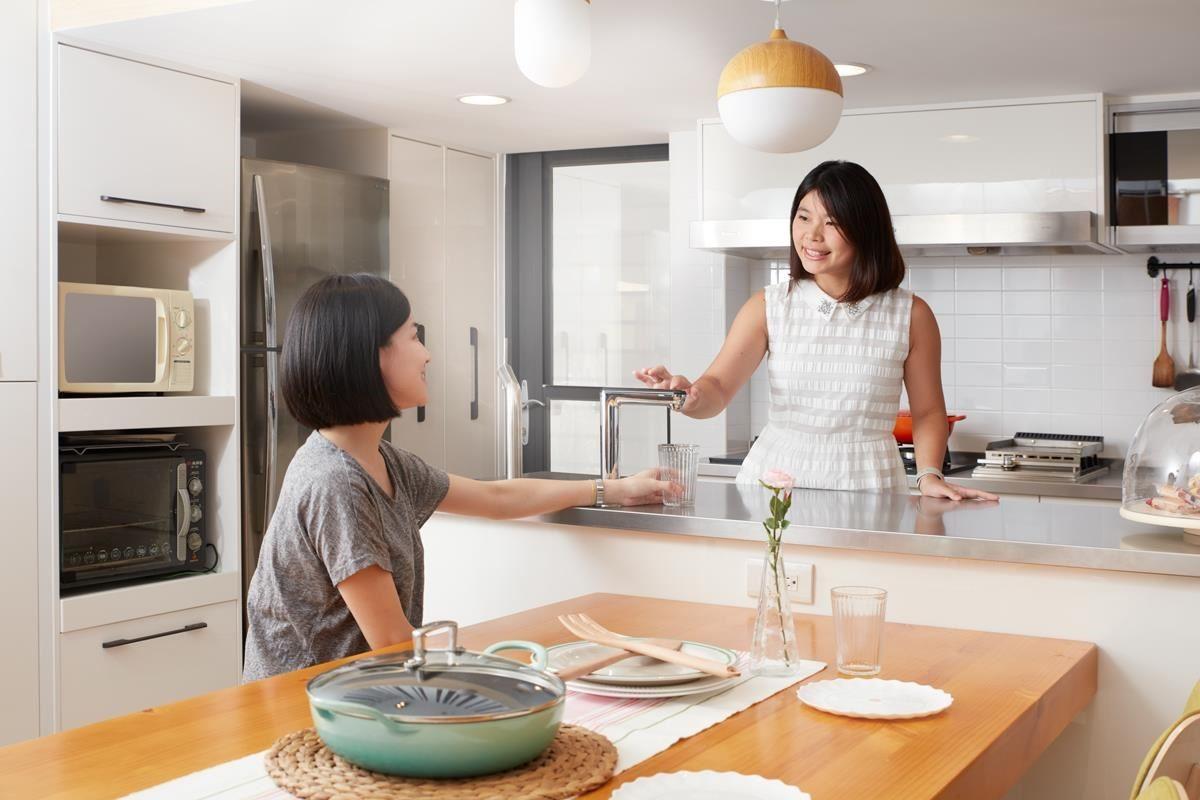 在餐桌的家人,只要將杯子遞放中島檯,即可取用飲用水。