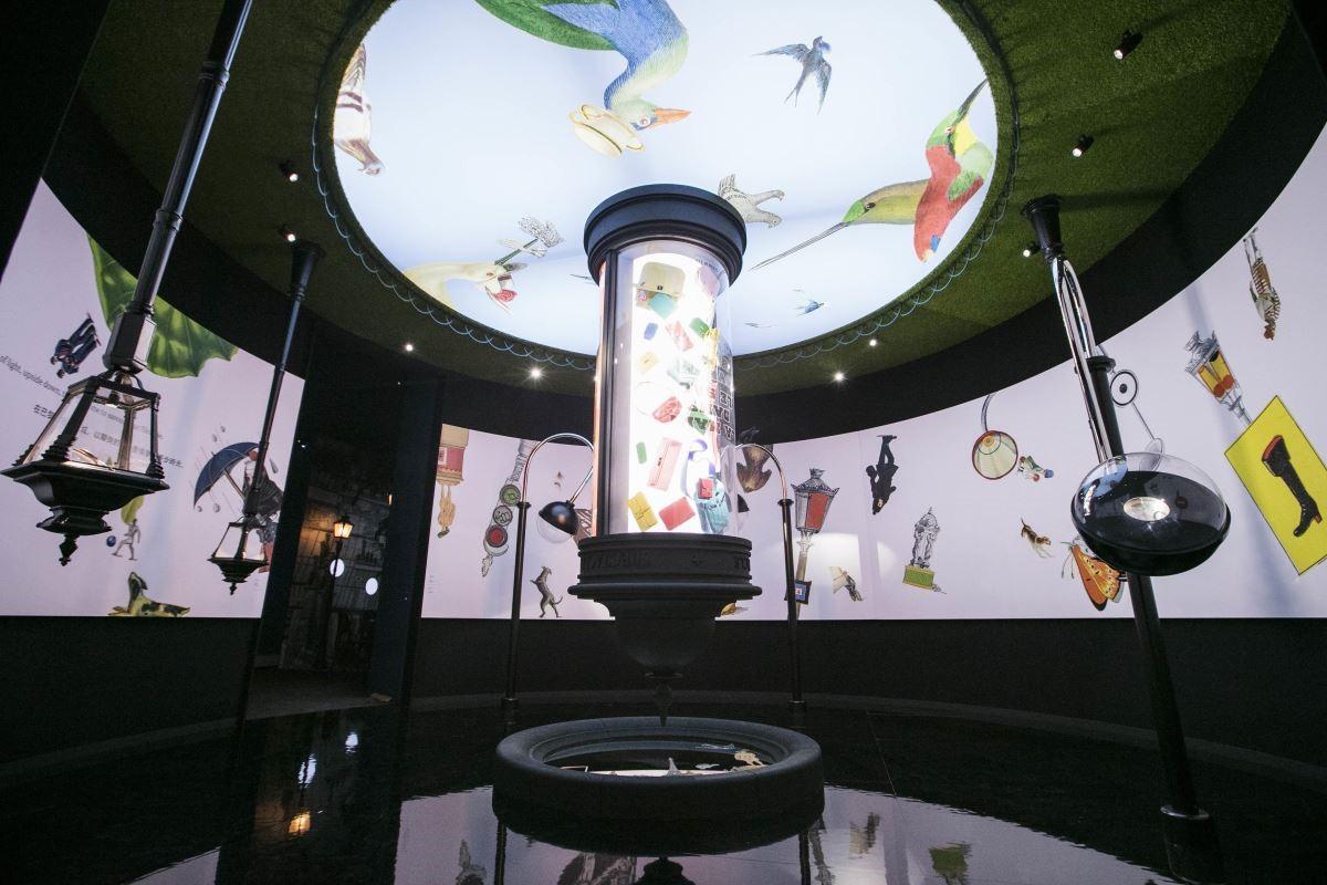巴黎街頭常見的莫里斯廣告柱,像照射過哆啦A夢的放大燈,巨大卻顛倒倒掛於〝廣場〞正中心,裡面隨興排列著五顏六色的手提包,兩旁的街燈內的燈泡則被愛瑪仕的古董鐘錶取代。(攝影_Mark Lee)