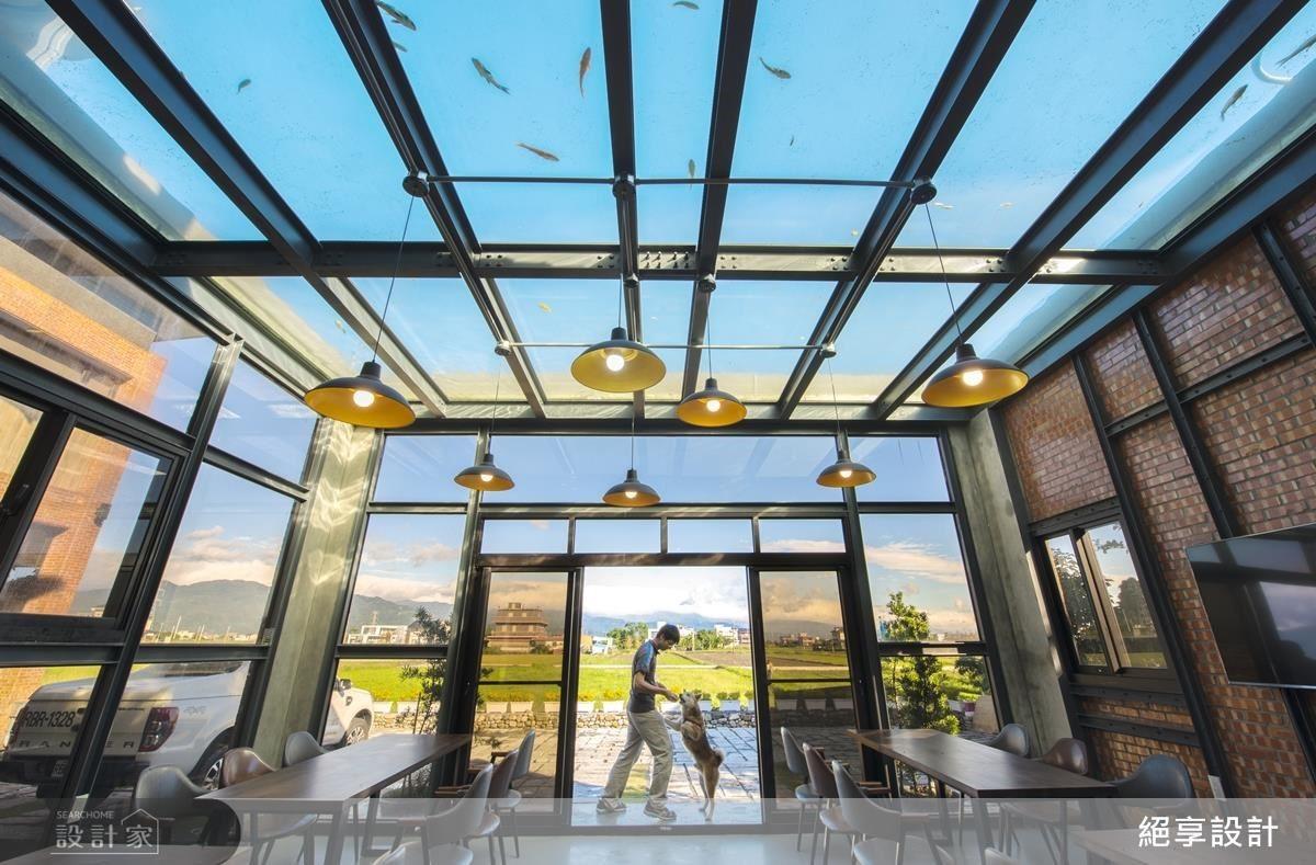 餐廳延續建築外觀工業風,有別於大廳的溫暖,採用玻璃打開空間,與戶外大自然結合,同時天花上方的魚池,讓室內空間有了不同的養分。