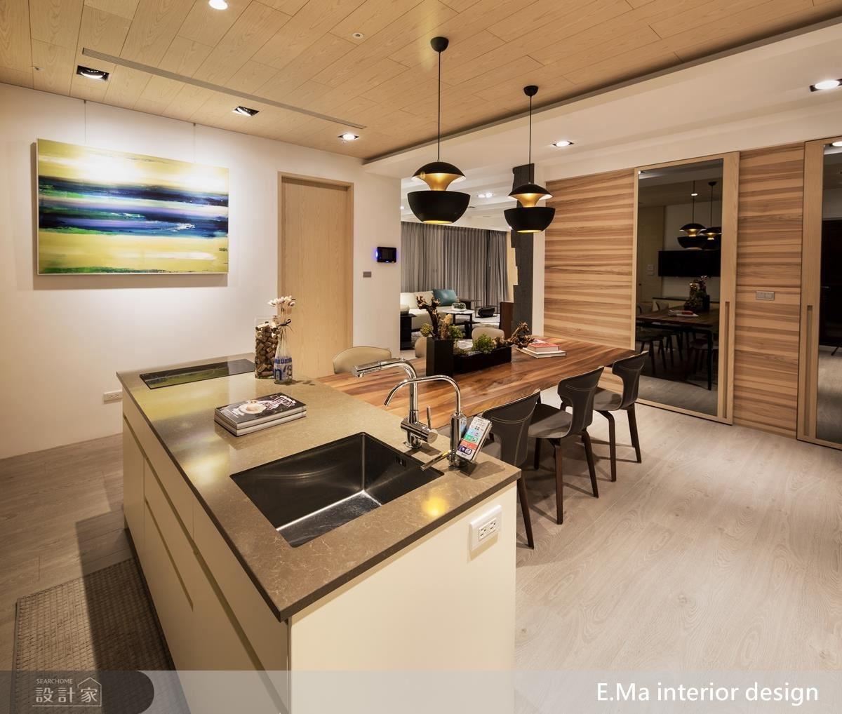 餐廚區使用加長型木桌搭配中島與系統廚具,滿足屋主好客習性。再利用灰鏡及淺木皮完美隱藏住多功能室及儲藏室。