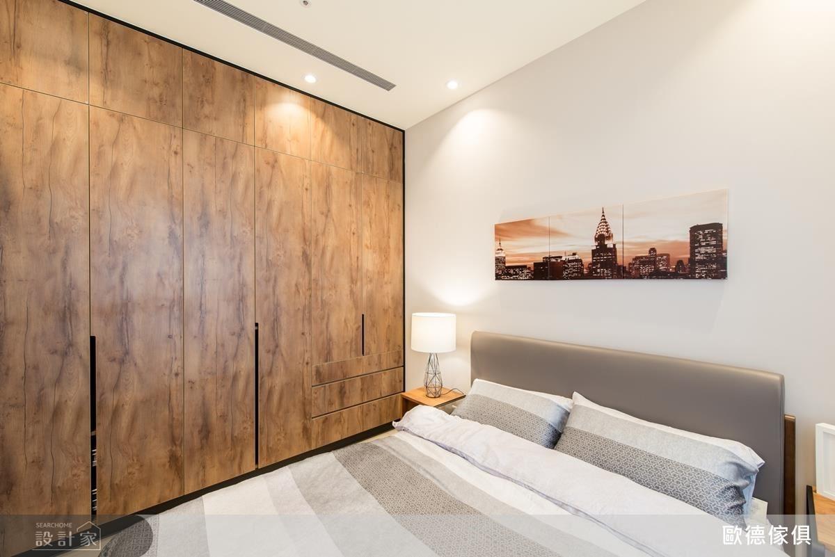 長親房中以淡褐色牆面,營造放鬆、恬靜的睡眠感。一旁以系統板材訂製大面櫃體,無把手的設計,讓空間更加遼闊、動線更加流暢。