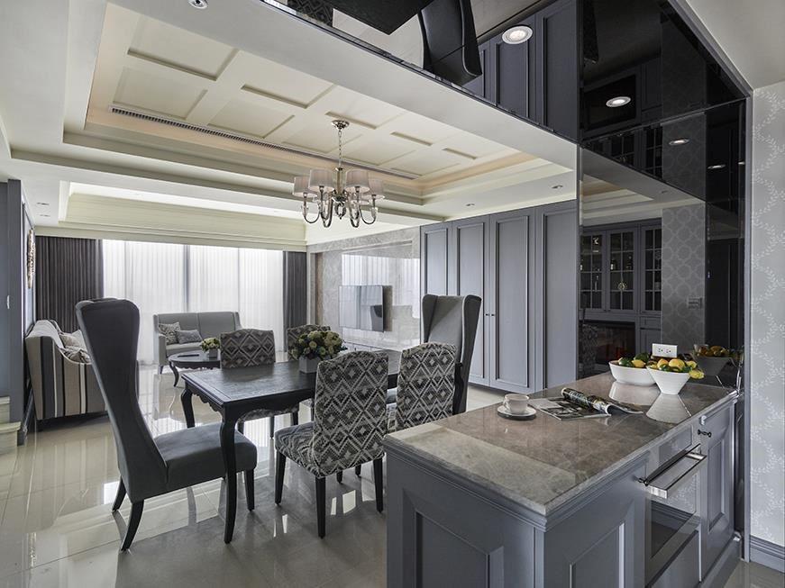 餐廚區以展示壁爐溫暖場域氛圍,牆面則在清淡優雅花紋的潤飾下顯現空間出眾氣質。餐廚交界則以灰鏡鋪設框面,巧妙化解天花樑柱也延伸出空間視覺美感。