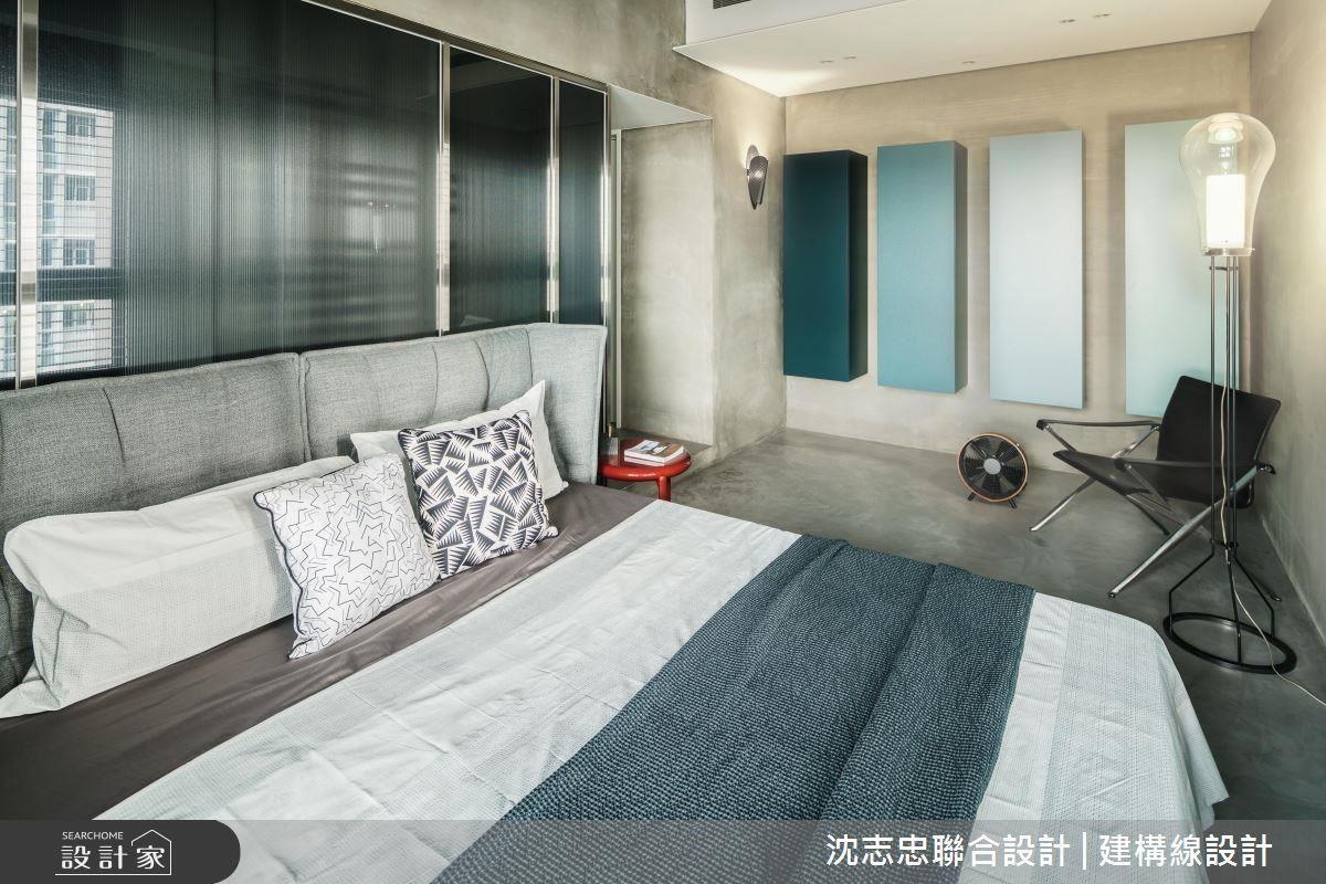 牆面與地板的淺灰水泥質感散發冷調與沉靜氣息,收納的規劃則以懸浮的矩形櫃體,以漸層藍色作視覺上的亮點,寢具與家具皆為冷色系,風格相當強烈。