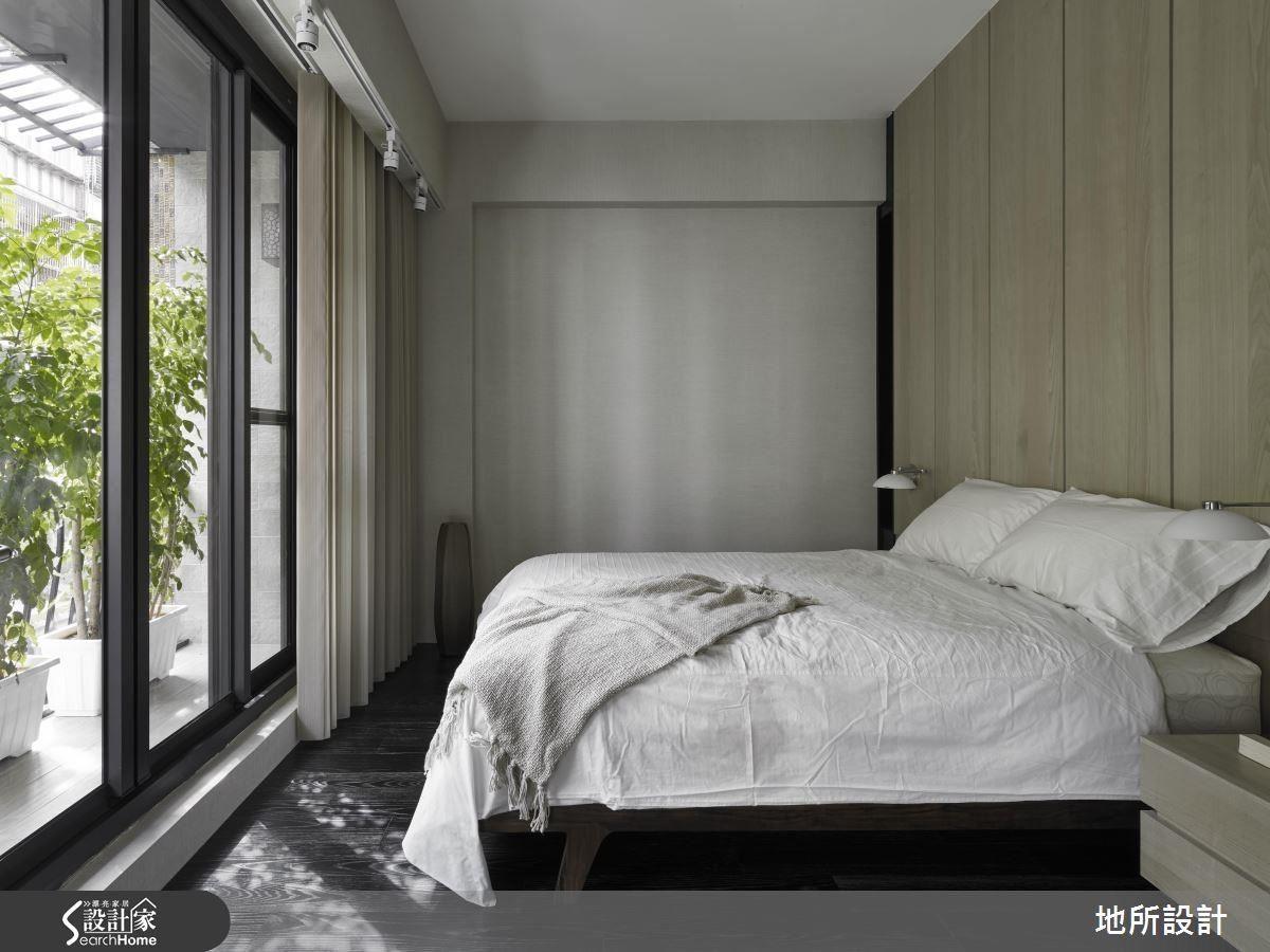 由於落地窗的採光與視野開放性相當良好,選用深色的木地板,加上淺色的寢具組,空間雖然不大卻完全不會有沉重的感受,落地窗外較大型的植栽,兼收增添綠意與些許隱私遮蔽的機能。