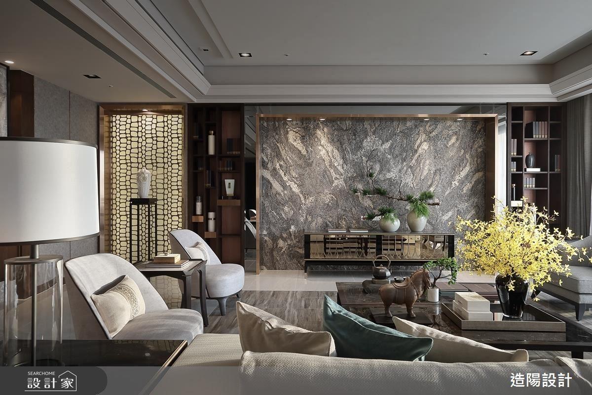 客廳主牆上如祥龍躍動般,卻曖曖內含光的珍貴石材黃金伊瓜蘇,為電視牆鋪敘宛如龍紋般的細緻,鍍鈦邊框則彰顯豪宅氣勢。