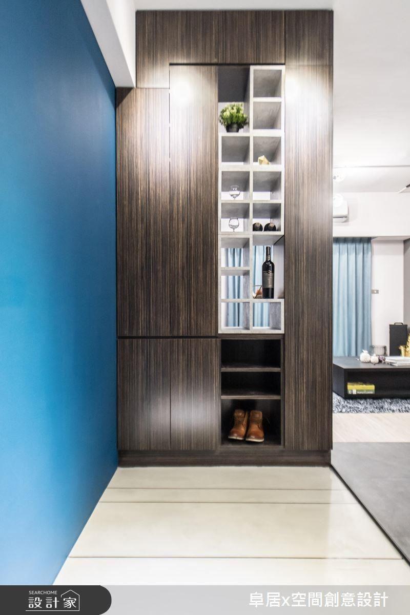 玄關運用鞋櫃作為屏風,同時以俄羅斯方塊的概念,堆疊出男屋主的紅酒櫃,並能隨著屋主心情及需求,變換櫃子的形狀和位置。