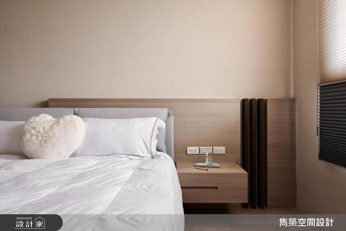 主臥床頭牆面以不規則深木格柵豐富視覺層次,並以奶茶色調溫暖睡眠感受。