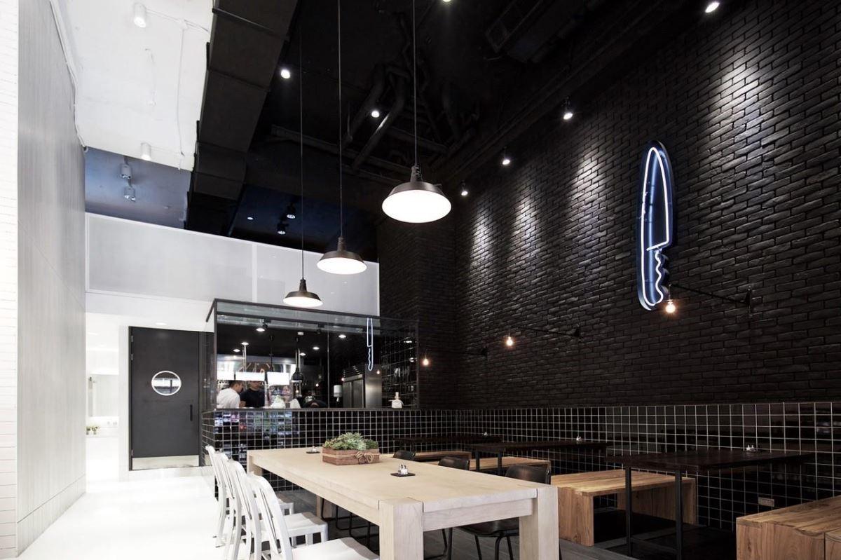 黑色座位區選用木色餐桌椅,營造用餐時的溫暖輕鬆感。