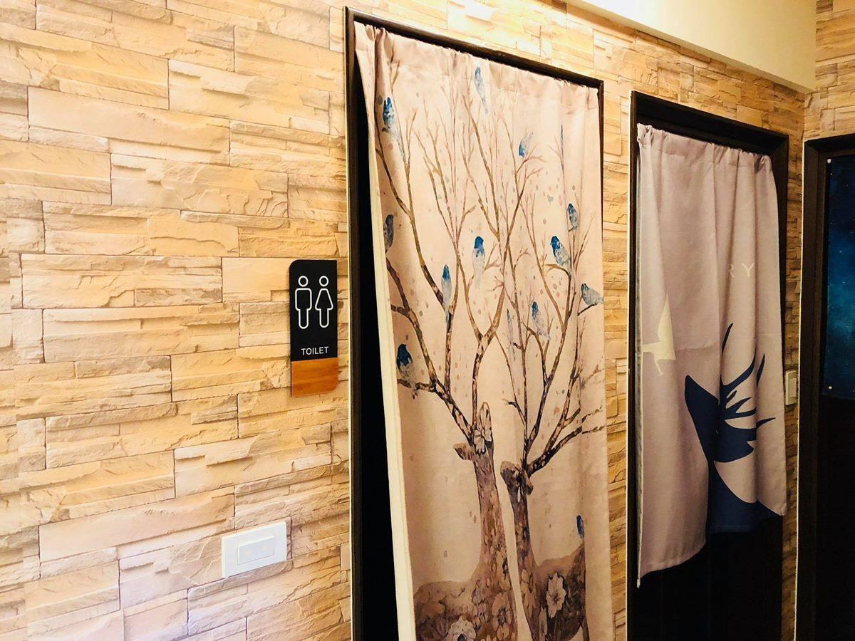 廁所外牆也貼上仿文化石壁布,搭配小巧的廁所指示牌,質感立刻提升。