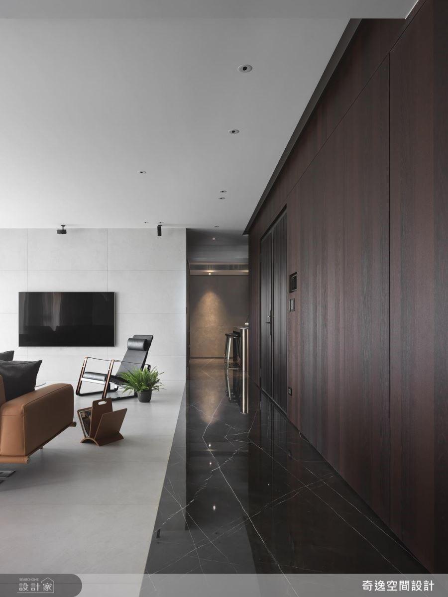 玄關地面以深色大理石對比公領域的淺色磁磚,藉由材質、色彩的鋪陳,巧妙界定空間場域。