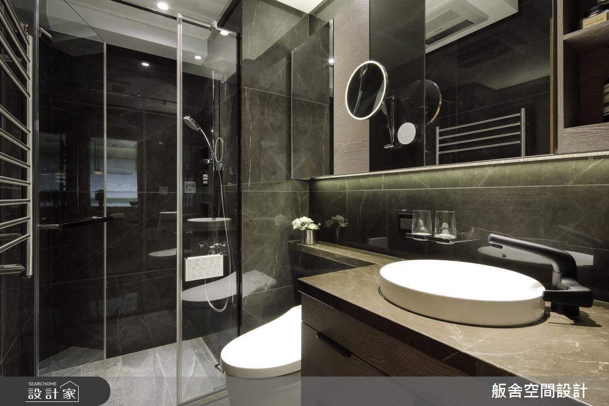 衛浴以深色磚打造質樸場域並增設櫃體豐富空間實用機能。